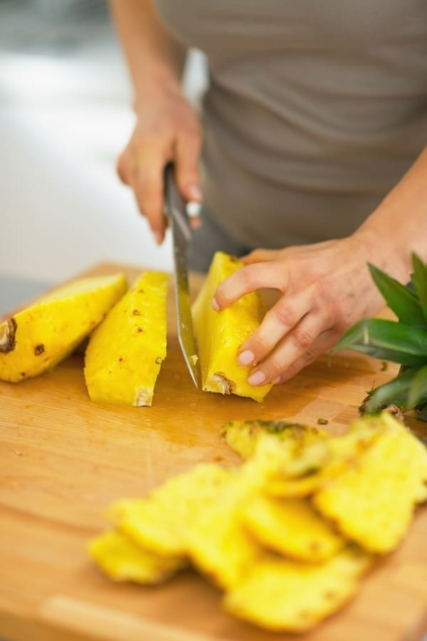 Cutting small pieces of pineapple to prepare it for dehydration